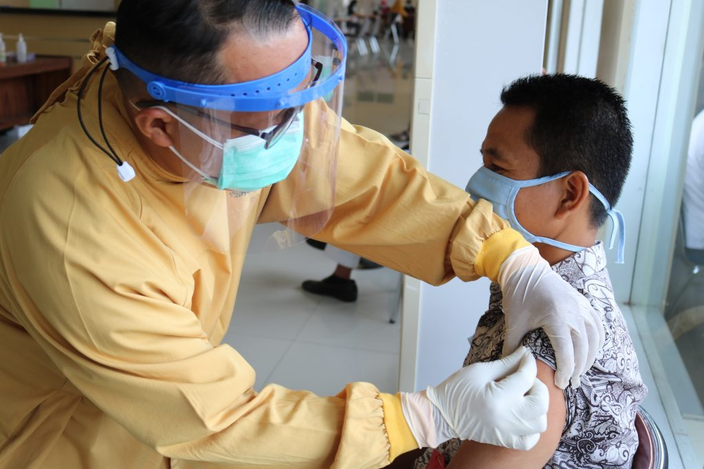 Mav is getting vaccinated by a healthcare care worker wearing protective gear